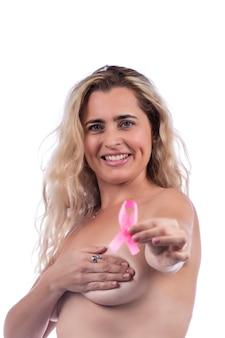 Mulher adulta cobrindo os seios com as mãos segurando uma fita rosa de conscientização do câncer de mama, sobre um branco.