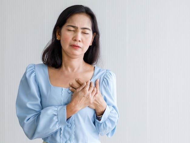 Mulher adulta com ataque cardíaco súbito e segurar o peito com dor no rosto. conceito de cuidados de saúde de emergência e afetados por insuficiência congestiva ou ressuscitação cardiopulmonar, problema cardíaco.