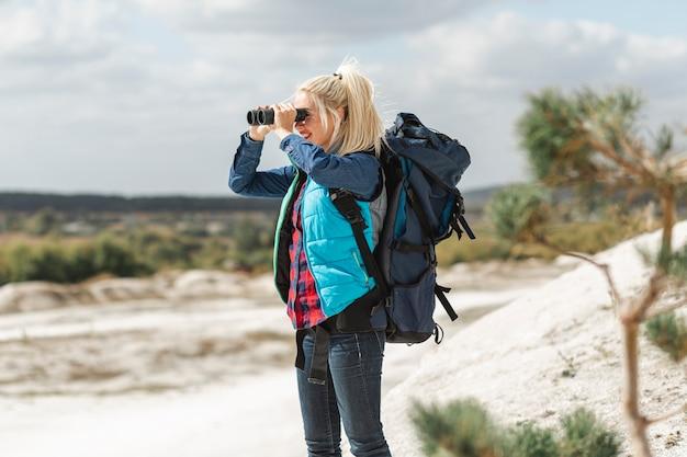 Mulher adulta com binóculos ao ar livre