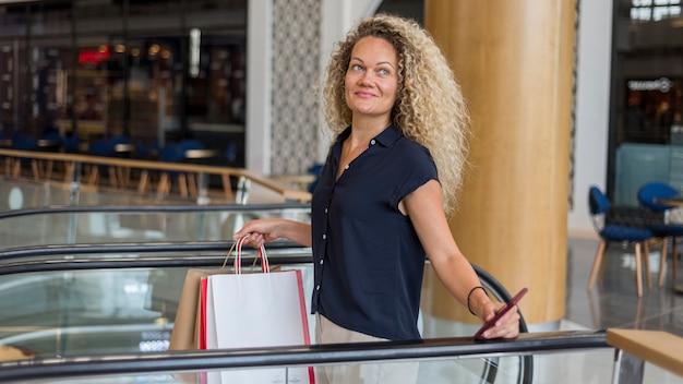 Mulher adulta com cabelo encaracolado carregando sacolas de compras