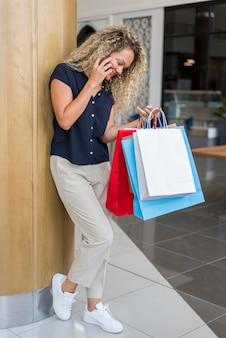 Mulher adulta com cabelo encaracolado segurando sacolas de compras