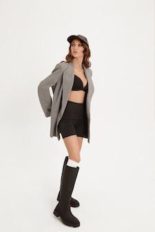 Mulher adulta com corpo perfeito vestindo uma jaqueta da moda, shorts e botas posando para o fundo branco isolado