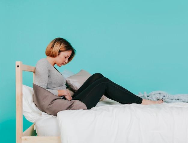 Mulher adulta com estômago ferido na cama