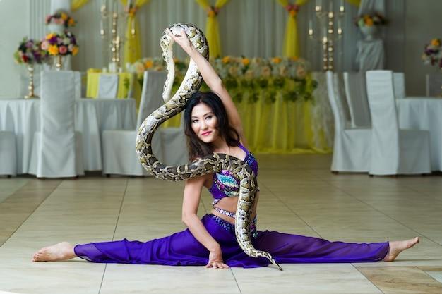 Mulher adulta com fantasia de palco azul se apresentando com cobra grande