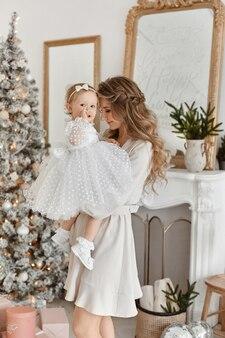 Mulher adulta com maquiagem macia e cabelos longos, posando com sua filha da criança fofa no interior decorado de natal.
