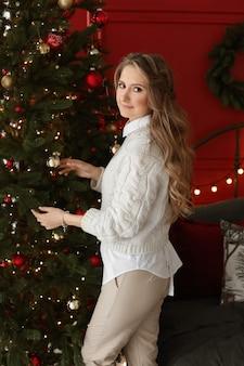 Mulher adulta com maquiagem macia e cabelos longos, vestindo roupas casuais, decorando a árvore de natal.