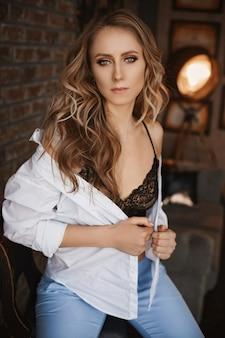 Mulher adulta com maquiagem perfeita e cabelo loiro em uma camisa branca desabotoada e sutiã preto posando no interior