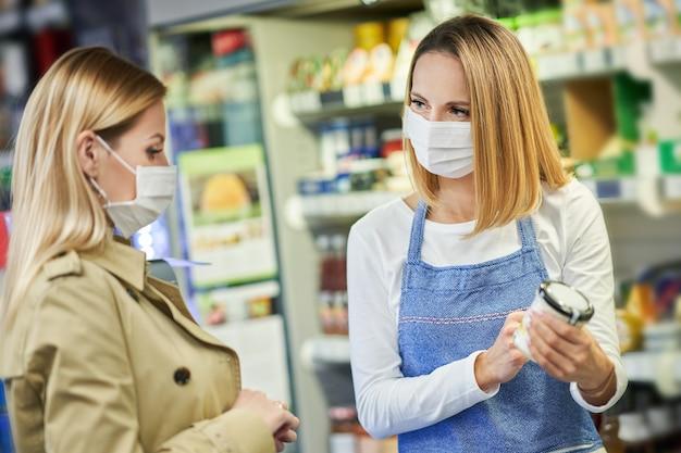 Mulher adulta com máscara médica comprando mantimentos