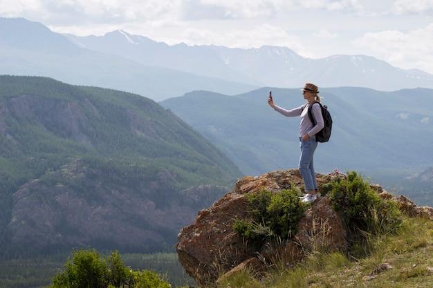 Mulher adulta com mochila alpinista tirando foto com telefone inteligente no pico da montanha. viagem e conceito de estilo de vida ativo.