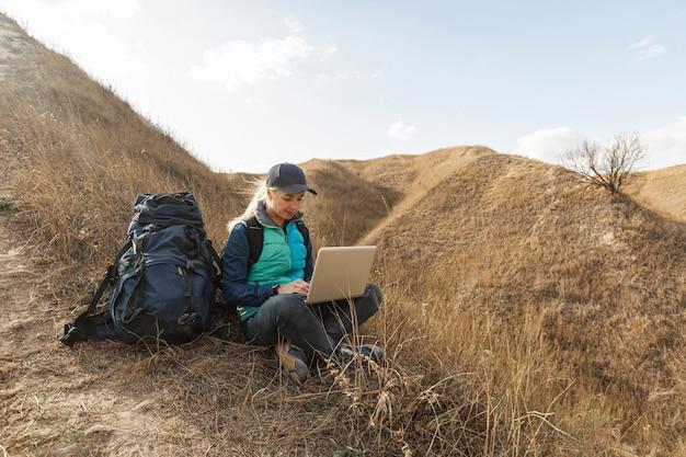Mulher adulta com mochila e laptop