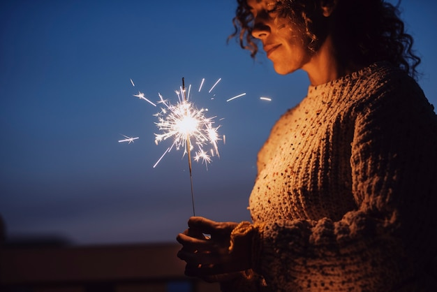 Mulher adulta com os olhos fechados segurando um diamante à noite com o céu azul ao fundo