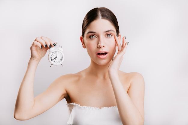 Mulher adulta com pele elástica e saudável, segurando um pequeno despertador branco.
