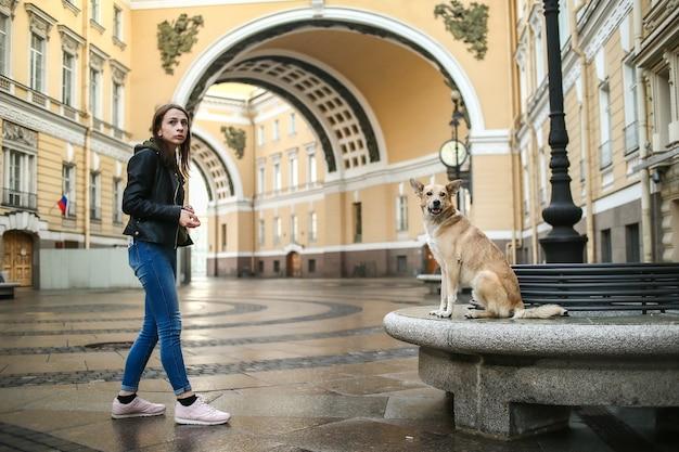 Mulher adulta com roupas casuais em pé com o cão pastor obediente na rua contra prédios antigos