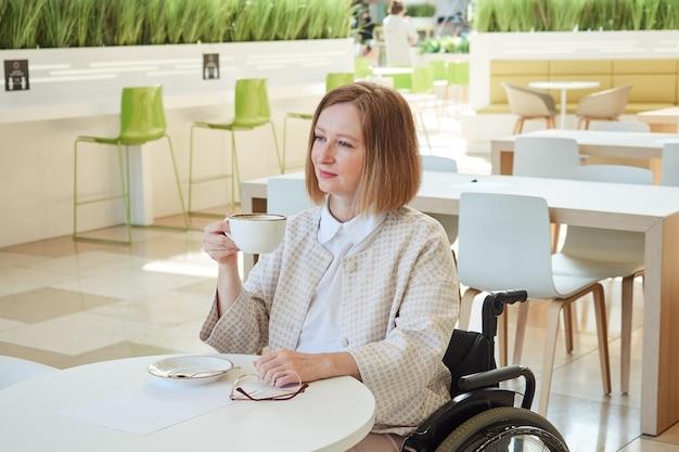 Mulher adulta com roupas leves bebe café no refeitório