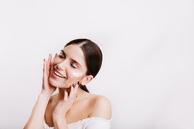 Mulher adulta com top branco cuida da pele do rosto, aplicando creme. retrato de menina com rabo de cavalo na parede isolada.