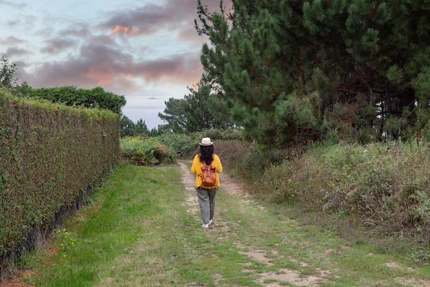 Mulher adulta com uma mochila de couro desce pelo caminho