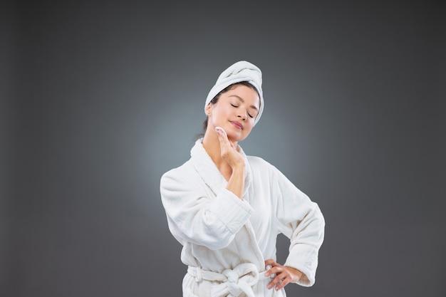 Mulher adulta confiante em um roupão de banho e uma toalha enrolada na cabeça com uma das mãos, usa uma almofada de algodão para limpar o rosto e pescoço, enquanto a outra mão se apóia em seu quadril