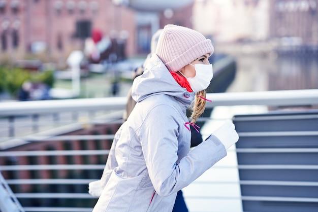 Mulher adulta correndo na cidade mascarada durante a pandemia de bloqueio