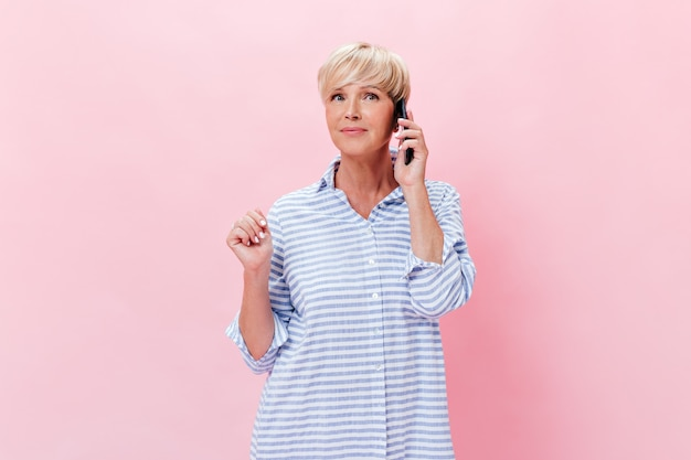 Mulher adulta de camisa azul falando ao telefone sobre fundo rosa