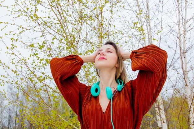 Mulher adulta de estilo com fones de ouvido e blusa cor de borgonha no fundo de árvores de vidoeiro