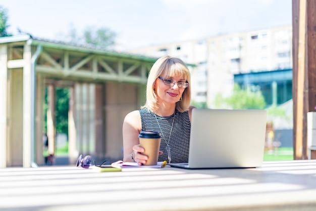 Mulher adulta de óculos, tendo a videochamada com o laptop do lado de fora no parque. feliz e sorridente sênior trabalhando e bebendo café.