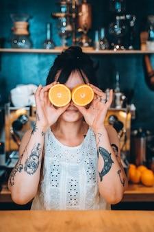 Mulher adulta de retrato segurando laranja na frente de olhos com sorriso.