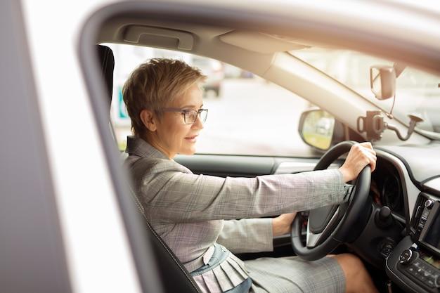 Mulher adulta de terno dirigindo um carro