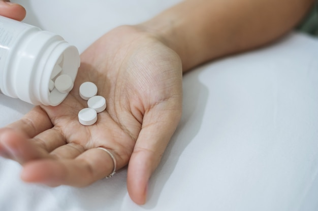 Mulher adulta derrama os comprimidos da garrafa, tomando remédio na cama de manhã em casa. conceito de enxaqueca, analgésico, dor de cabeça, gripe, doença, doença e cuidados de saúde