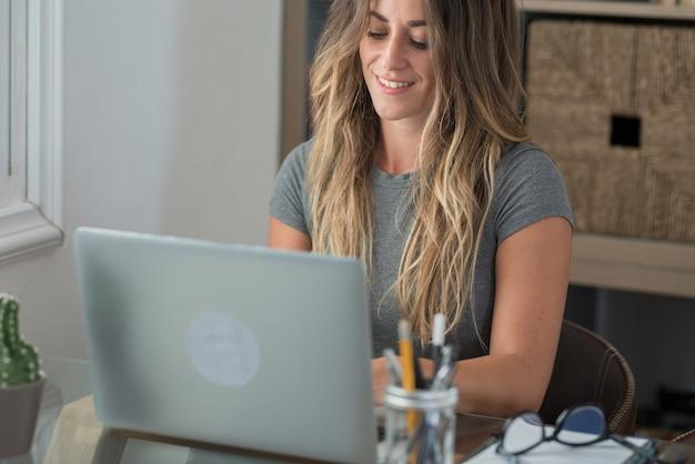 Mulher adulta digita no laptop e sorri feliz pelo trabalho inteligente, atividade doméstica, escritório grátis - pessoas modernas, trabalho online, trabalho remoto, estilo de vida - mulher, meia-idade