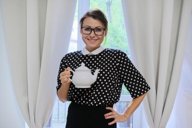 Mulher adulta, dona de casa com bule, mulher segurando um bule de porcelana branca nas mãos, em casa perto da janela com cortinas, hora do chá