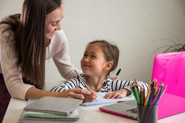 Mulher adulta e garota étnica sorrindo e olhando uma para a outra enquanto escrevem no caderno durante a aula online em casa juntas