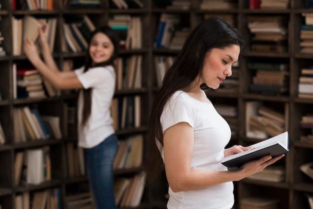 Mulher adulta e menina procurando livros na biblioteca
