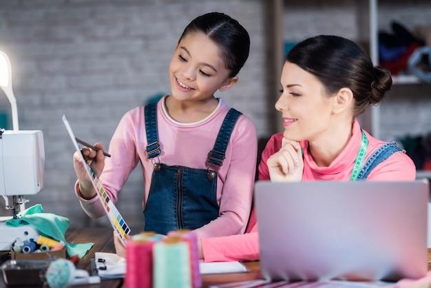 Mulher adulta e uma menina estão escolhendo uma cor.