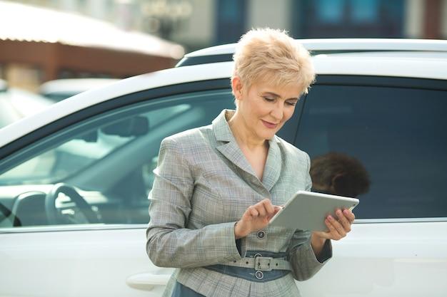 Mulher adulta elegante de terno com tablet perto do carro
