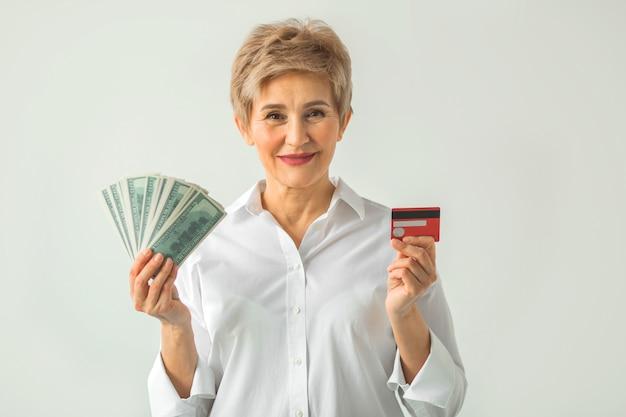 Mulher adulta elegante em uma camisa branca em um fundo branco com dólares e um cartão de crédito