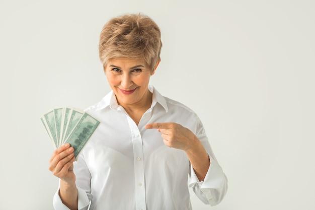 Mulher adulta elegante em uma camisa branca em um fundo branco com dólares na mão