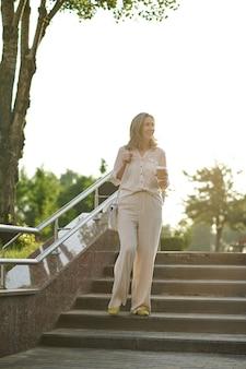 Mulher adulta elegante na escada do parque