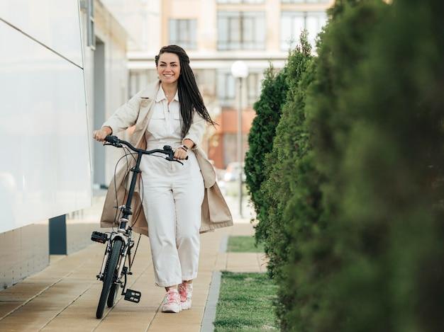 Mulher adulta elegante posando com bicicleta ecológica