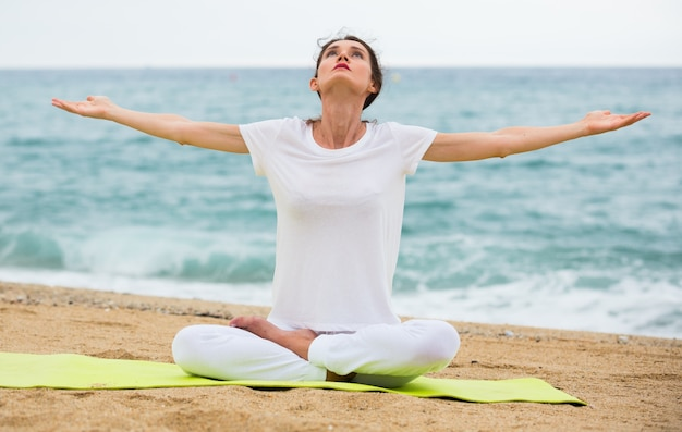 Mulher adulta em camiseta branca está sentada e praticando asana