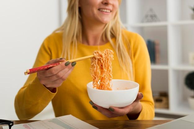 Mulher adulta em close comendo macarrão