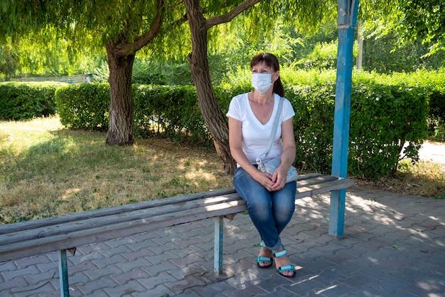Mulher adulta em máscara protetora senta-se sozinho em um ponto de ônibus vazio