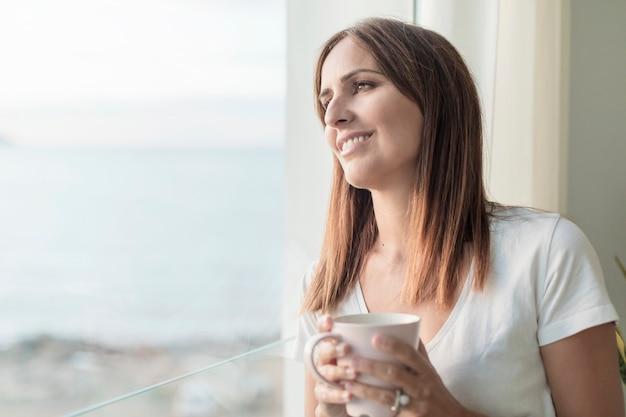 Mulher adulta em pé enquanto olha pela janela, degustação de café