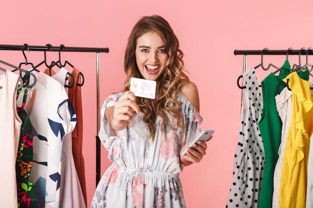 Mulher adulta em pé perto do guarda-roupa, segurando um smartphone e um cartão de crédito isolado em rosa
