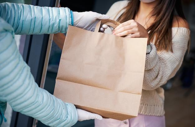 Mulher adulta em quarentena com máscara facial recebe entrega de comida em casa