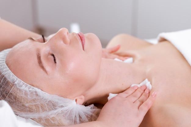 Mulher adulta em uma clínica de cosmetologia em procedimento facial de rejuvenescimento
