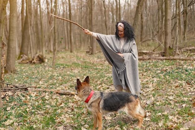 Mulher adulta em uma floresta de primavera com cachorro