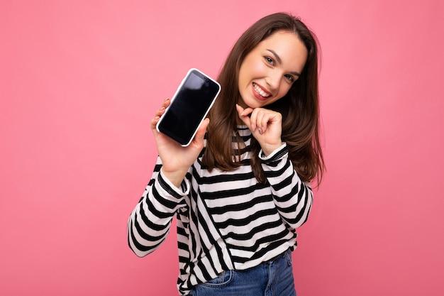 Mulher adulta engraçada encantadora vestindo um suéter listrado isolado na parede com espaço de cópia mostrando a tela do telefone móvel. mock up, cutout