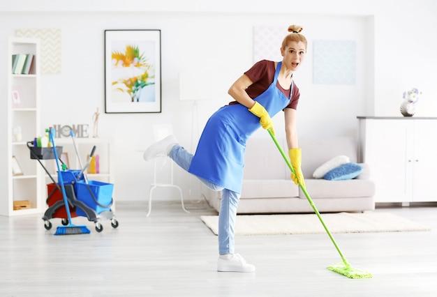 Mulher adulta engraçada esfregando o chão na sala de estar
