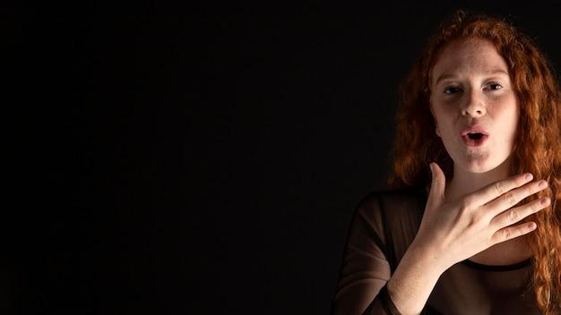 Mulher adulta ensinando linguagem de sinais com espaço de cópia