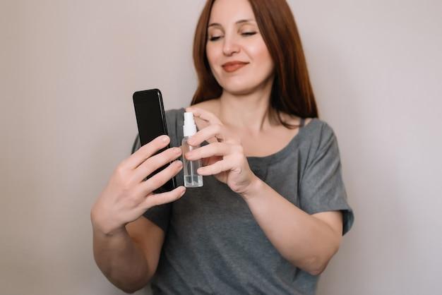 Mulher adulta está pulverizando álcool, spray desinfetante no celular, previne a infecção do vírus covid-19